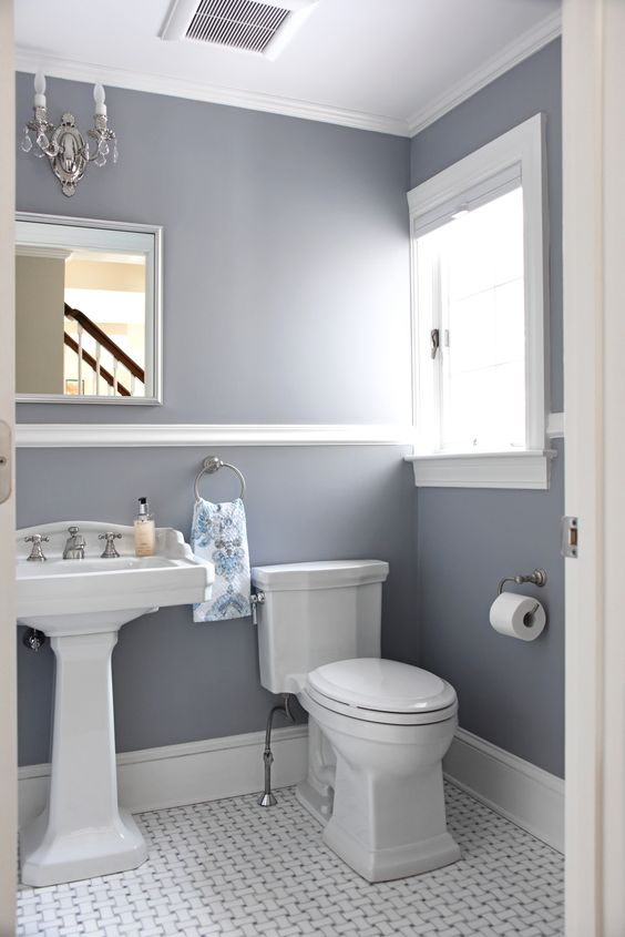 a pretty powder room with grey walls, a pedestal sink, vintage sconces and floral towels is a very chic and cool space