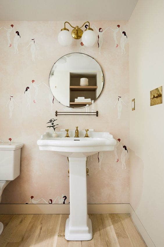 a pretty powder room with pink printed wallpaper, a pedestal sink, a round mirror, sconces, brass touches for a chic touch