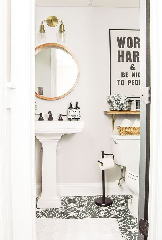 a pretty small powder room with black and white tiles, a pedestal sink, a round mirror in a wooden frame, a shelf and black fixtures