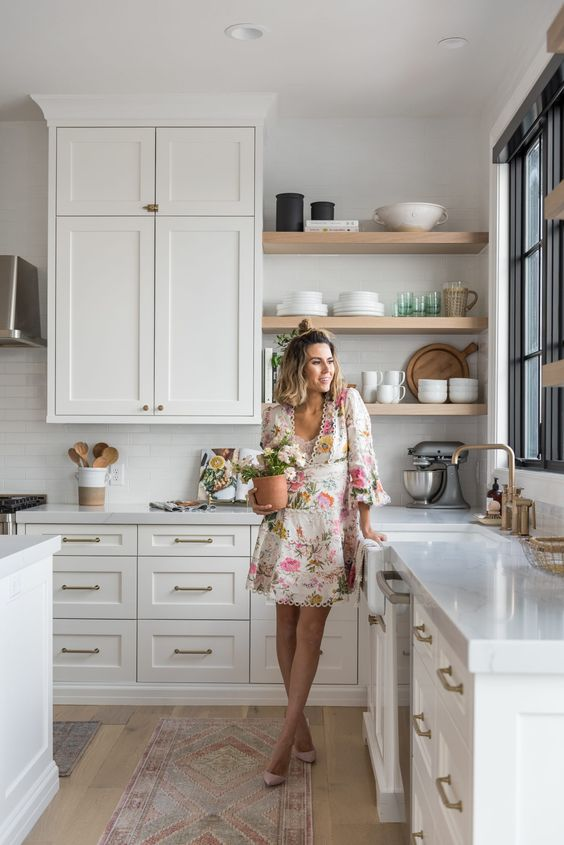 a pretty white farmhouse kitchen with shaker cabinets, floating shelves, metallic touches and a window in a black frame