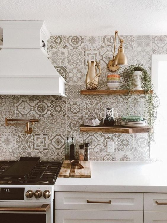 a pretty white kitchen with shaker cabinets, a grey and white Moroccan tile backsplash and stained open shelves