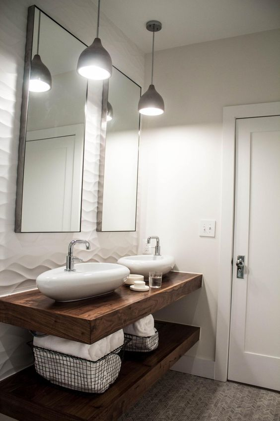 a refined bathroom with a wave accent wall, dark stained wooden shelves, oval stone vessel sinks, pendant lamps and a duo of mirrors