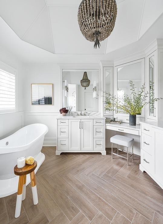 a refined bathroom with a wood look tile floor, a chic vanity, a tub, a beaded pendant lamp, a floating makeup vanity and a stool