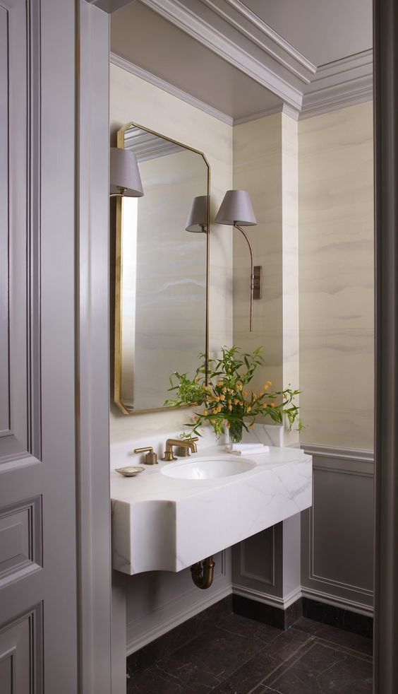 a refined bathroom with grey panels on the walls, neutral wallpaper, a floating stone sink, a mirror in a gidled frame and grey sconces