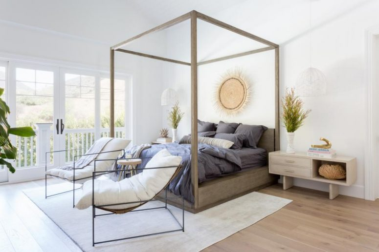 a refined bedroom with a stained canopy bed, navy bedding, chic loungers, potted plants and matching nightstands