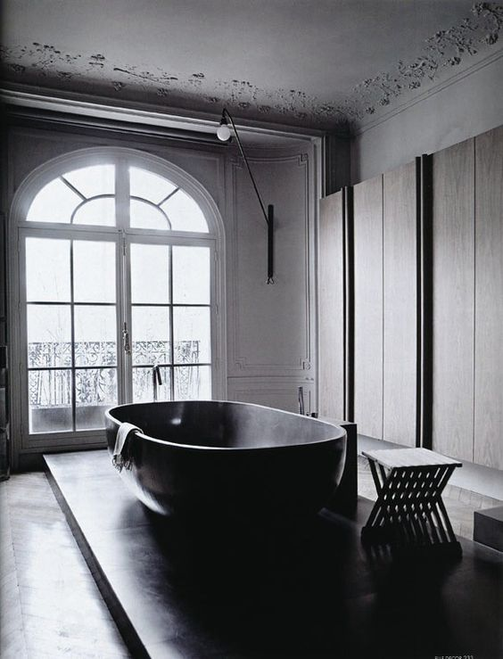 a refined contemporary bathroom with sleek storage units, a platform with a large bathtub and a black stool is amazing