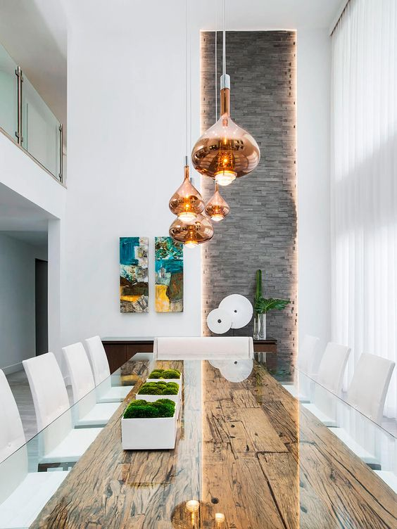 a refined dining space with a reclaimed wood table and a glass tabletop, copper pendant lamps and potted moss is amazing