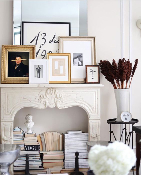 a refined fireplace with a gallery wall on the mantel, with books and statues inside it is a very chic and cool idea