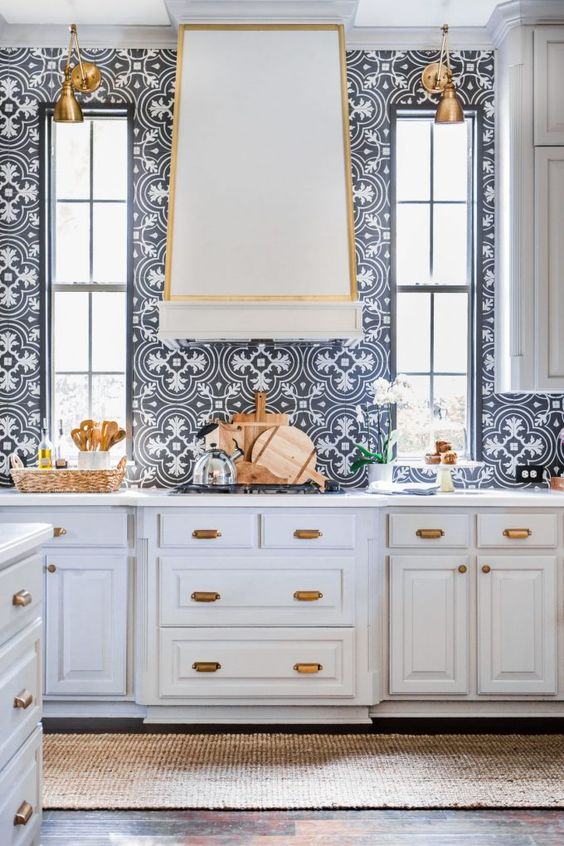 a refined formal white kitchen with shaker style cabinets, with gold touches for a chic feel and navy and white Moroccan tiles on the backsplash