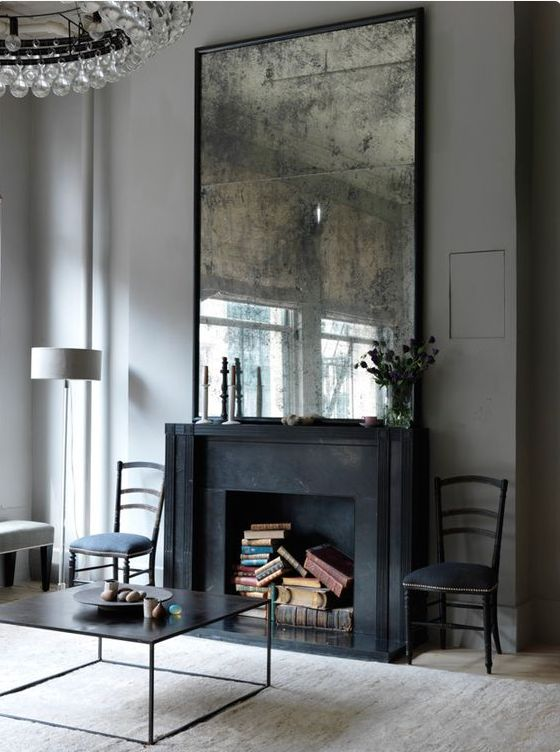 a refined living room with a black fireplace that is sued for book storage and a vintage mirror for a more exquisite look in the space