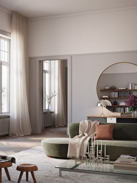 a refined living room with a grene rounded low sofa, a glass coffee table, wooden stools and a large round mirror
