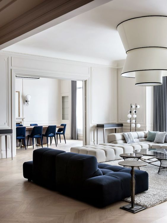 a refined living room with a large neutral sectional and a navy low sofa, a cool chandelier, a small desk and round tables