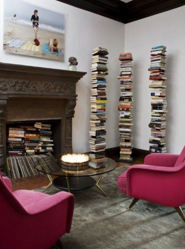 a refined living room with a vintage fireplace with lot sof books and magazines, with book stacks, with bold pink chairs and a round glass table