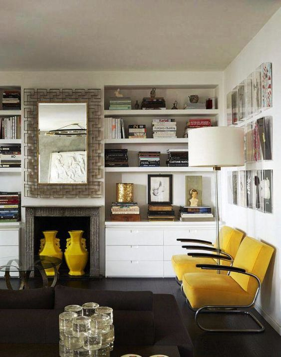 a refined living room with built-in shelves, yellow chairs, a built-in fireplace and yellow vases, a gallery wall and a floor lamp