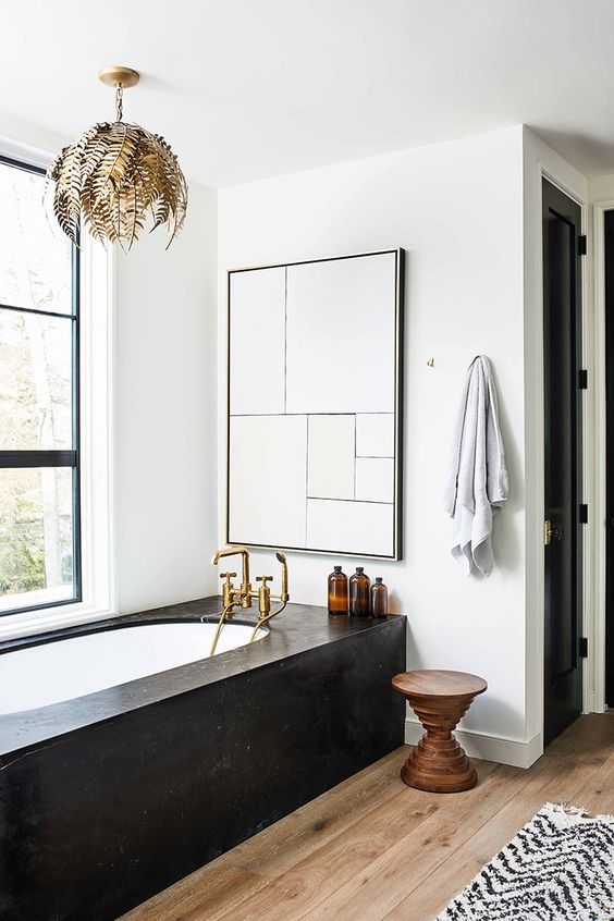 a refined modern bathroom with a tub clad with black stone, a wooden stool, a chic gold leaf chandelier and a large window