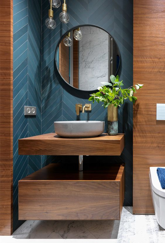 a refined modern bathroom with blue and teal chevron tiles, plywood touches and a vanity, a white stone vessel sink and a round mirror