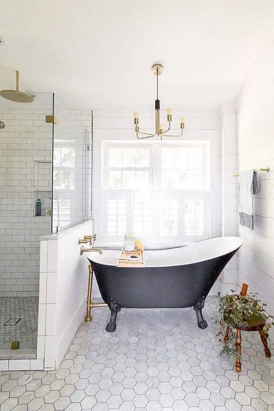a refined modern bathroom with subway and hex tiles, a planked wall, a black vintage bathtub and a chic gilded chandelier