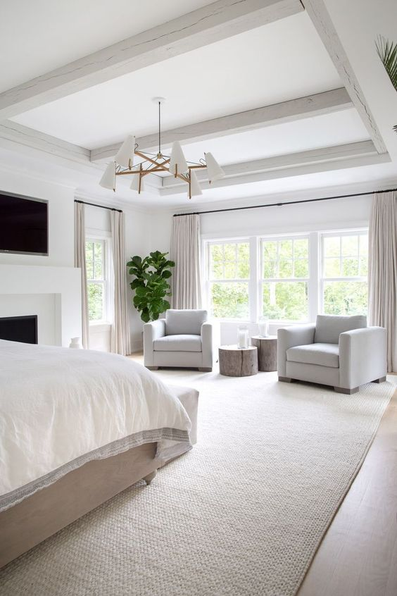 a refined neutral bedroom with wooden beams, a fireplace, a bed and white chairs, potted plants and a chic chandelier
