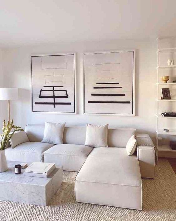 a refined neutral living room with a creamy sectional, a duo of artworks and an open shelving unit, a white marble slab table