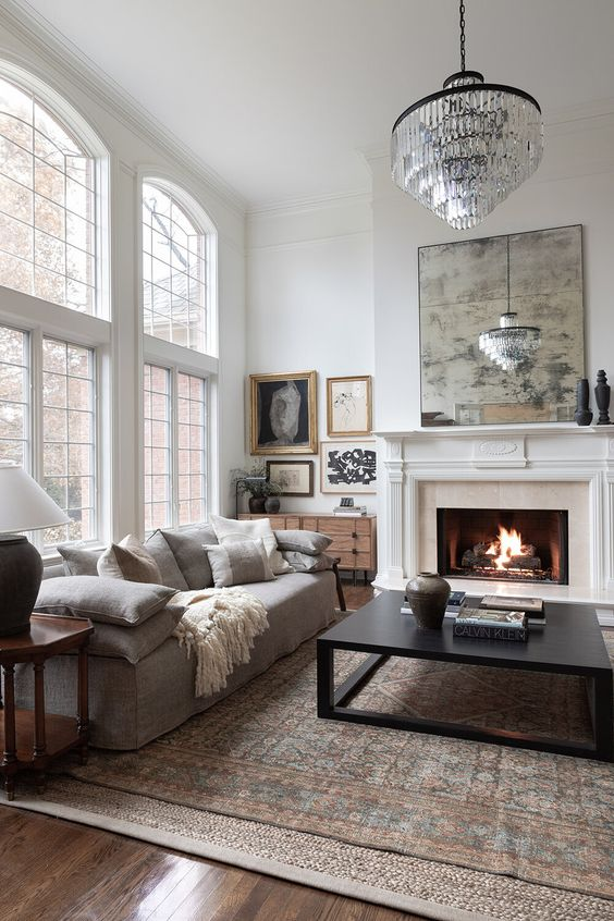 a refined neutral living room with a low grey sofa with lots of pillows, a low coffee table, a fireplace, a crystal chandelier and a gallery wall