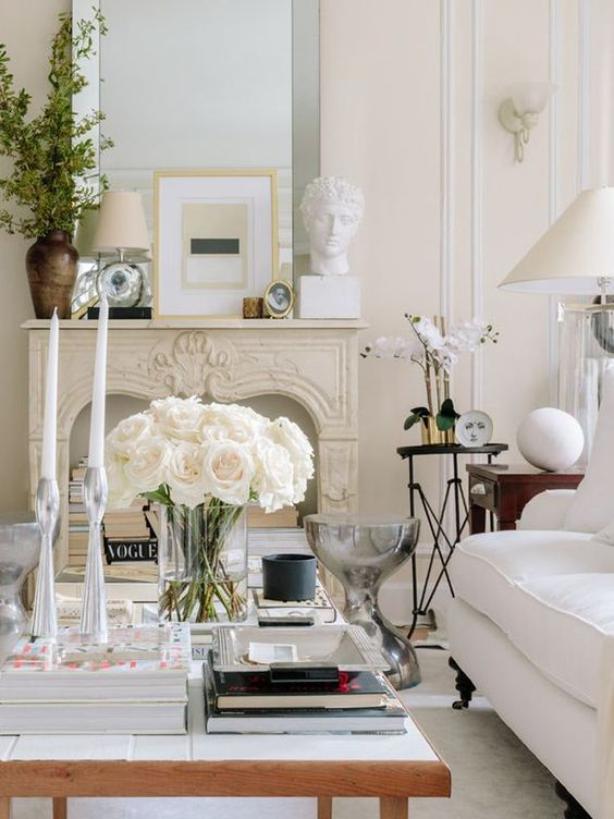 a refined neutral living room with creamy walls and furniture, with a low coffee table, a chic mantel and books in the fireplace plus an oversized mirror