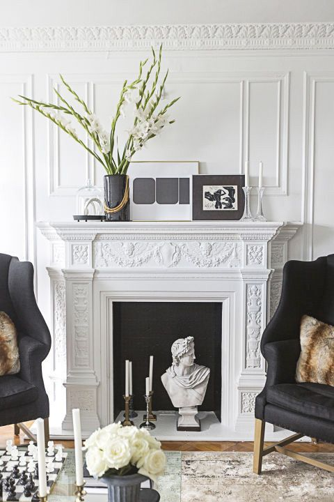 a refined neutral space with molding, with a statue, candles, white blooms in a black vase and artworks plus black chairs