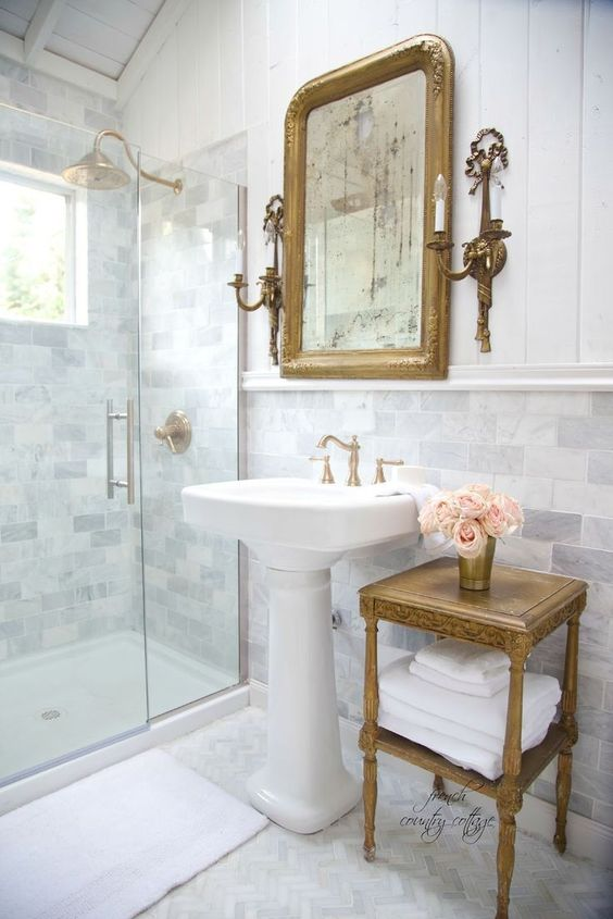 a refined vintage bathroom clad with marble subway tiles, a vintage pedestal sink, a vintage tiered table, a mirror in a gilded frame and vintage fixtures