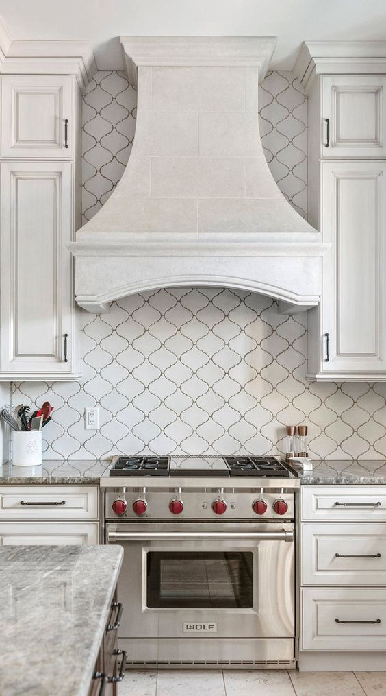 a refined vintage white kitchen with shaker style cabinets, a white arabesque tile backsplash and a vintage hood plus built-in appliances