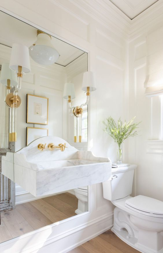 a refined white bathroom with paneled walls, a mirror and a floating stone sink attached to it, some sconces and lamps and white appliances