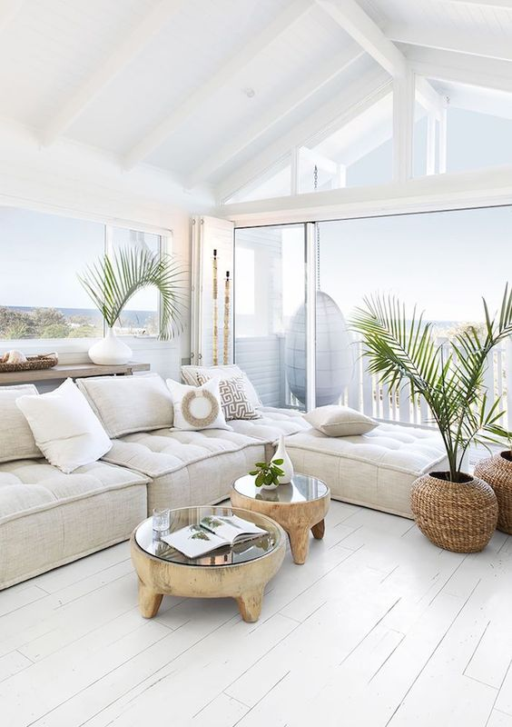 a relaxed coastal living room in white, with a low sectional, wood and glass coffee tables and potted plants plus a sea view