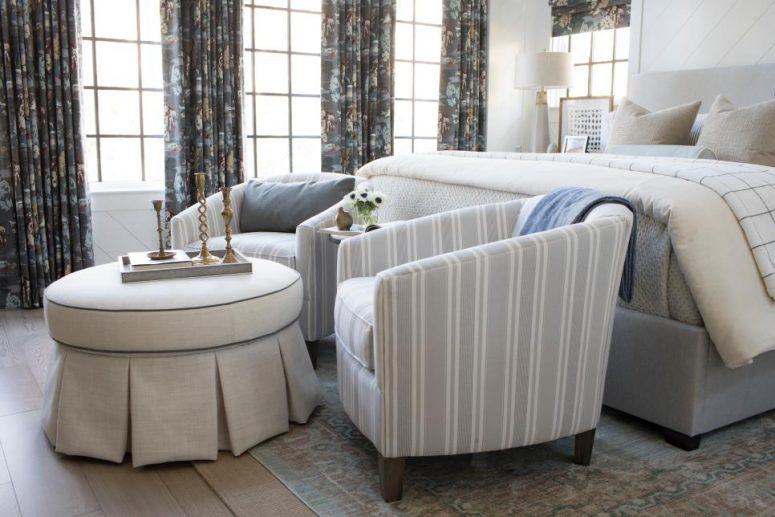 a retro bedroom with statement dark printed curtains, a neutral bed and striped chairs, a round ottoman and candlesticks