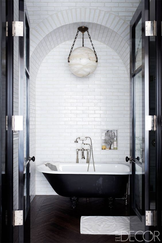 a retro black and white bathroom with white subway tiles, a black clawfoot tub, a pendant lamp and a niche for storage