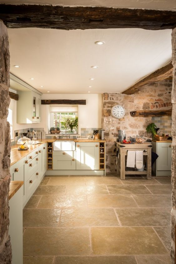 a rustic kitchen with stone walls, wooden beams, light grey cabinetry, butcherblock countertops and built-in lights is cool