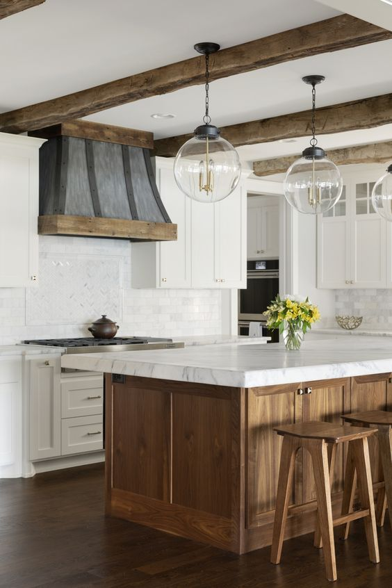 a rustic kitchen with white shaker cabinets, a stained wood kitchen island, white stone countertops, a wooden hood and pendant lamps