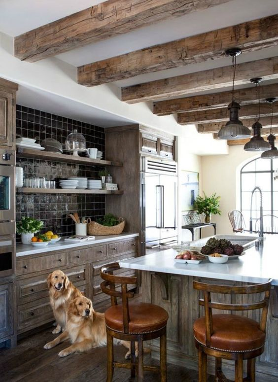a rustic kitchen with wooden beams that match stained kitchen cabinetry, a black tile backsplash and a row of pendant lamps