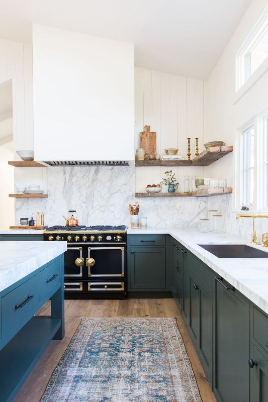 a rustic meets glam kitchen with blue cabinetry, white open shelves, a large hood and a bold black cooker