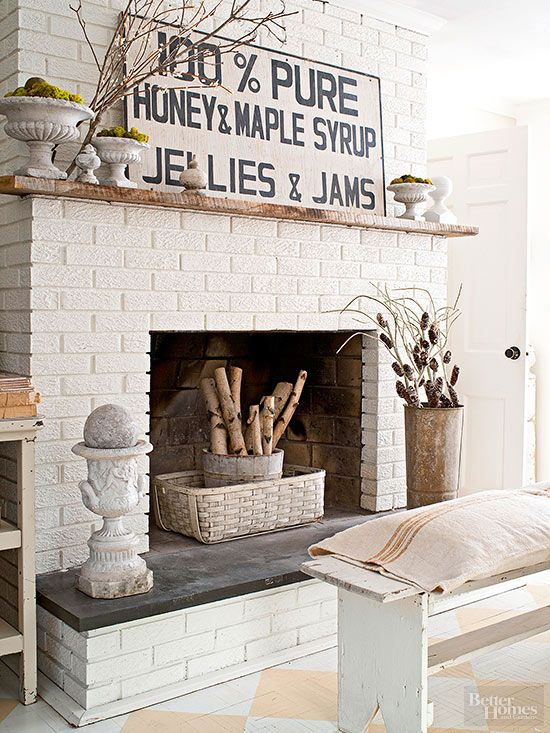 a rustic white brick fireplace with a basket, a bucket with branches, vintage urns and moss, pinecones and branches