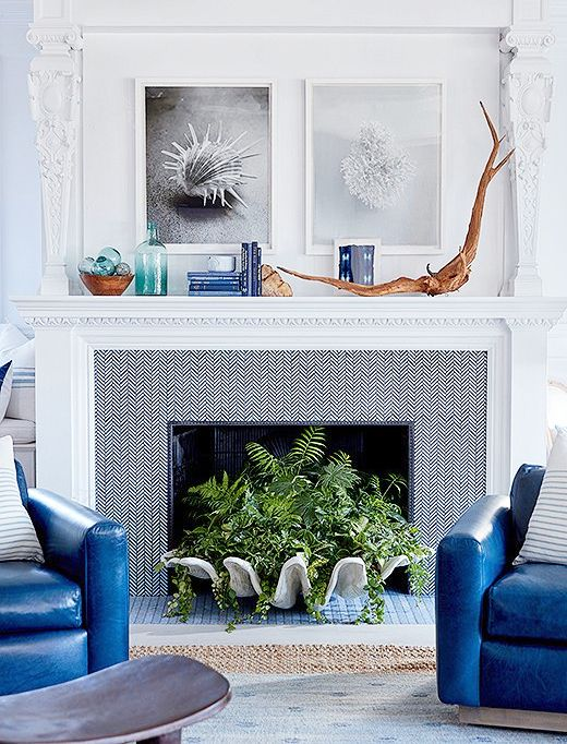 a seaside living room with bold blue chairs, a fireplace with chevron wallpaper, a large seashell with greenery, driftwood, artworks and bottles