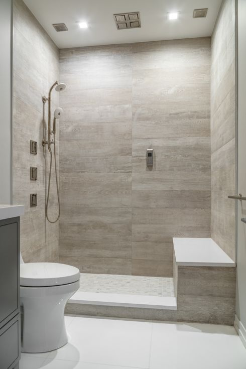 a serene contemporary bathroom clad with wood look and white tiles, built-in lights and white appliances is a chic and cool idea