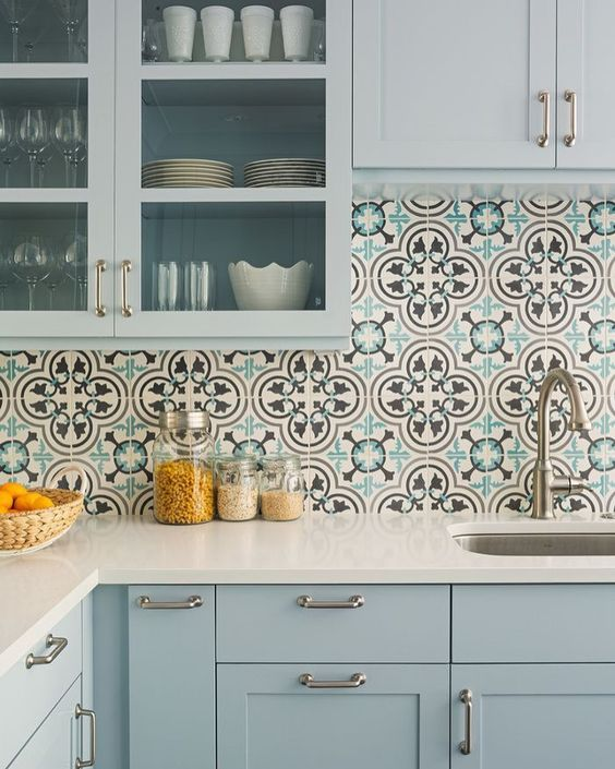a serene light blue kitchen with white countertops, a Moroccan tile backsplash and glass cabinets to look more lightweight