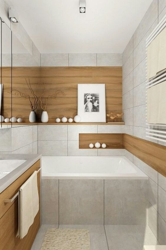 a serene minimalist bathroom clad with neutral large scale tiles and wood look ones, with a wooden vanity, some candles and an artwork