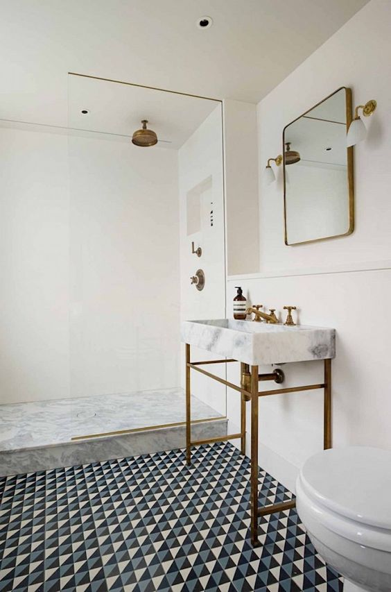 a serene modern bathroom with a geometric floor, a console sink,a shower space clad with stone and neutral tiles, touches of brass is chic