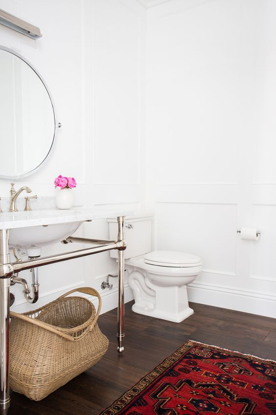 a serene powder room in white, with a dark floor, a bold rug, a console sink, a round mirror and white appliances is a cool idea