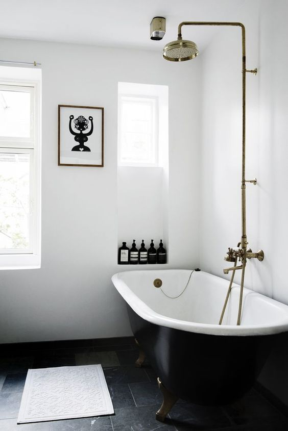 a serene white bathroom with niches for storage, a black clawfoot bathtub, brass fixtures and a fun artwork is cool