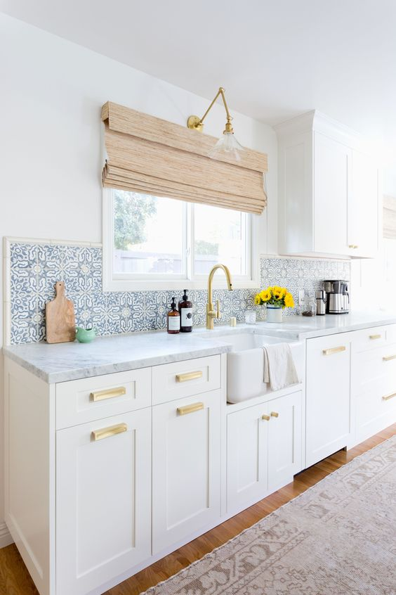 a serene white farmhouse kitchen with shaker cabinets, with white marble countertops and blue Moroccan tiles on the backsplash