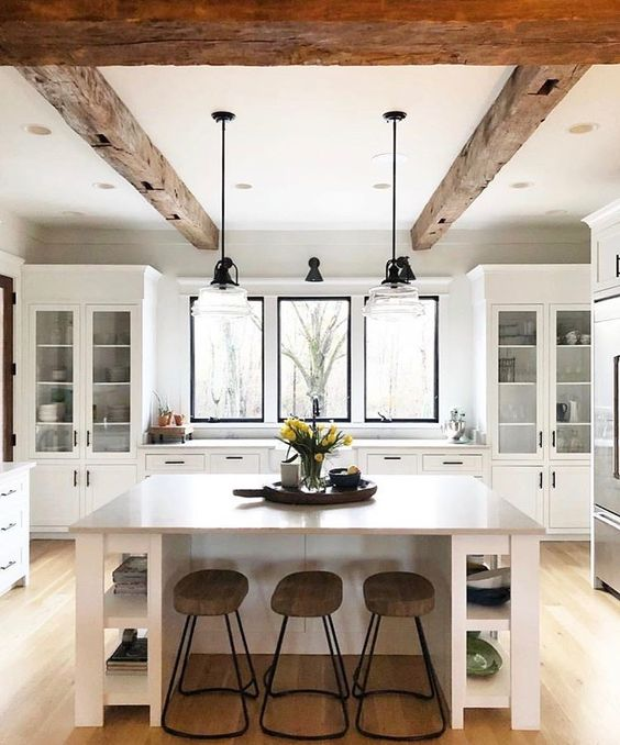 a serene white kitchen with glass cupboards and windows instead of a backsplash, a large kitchen island with open storage
