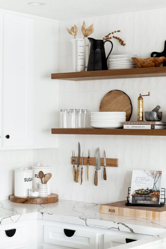 a serene white kitchen with shaker cabinets, a white tile backsplash and white stone countertops, stained floating shelves