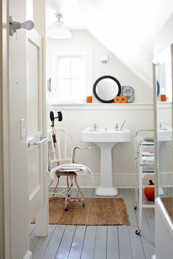 a shabby chic bathroom with neutral walls and grey planked floors, a pedestal sink, a round mirror, a vintage chair and a cart with glass shelves