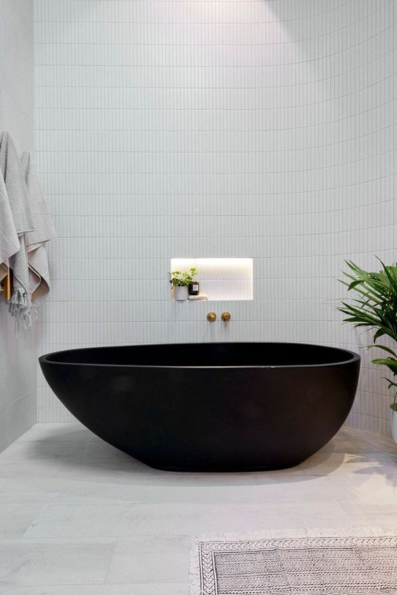 a sleek contemporary bathroom with large scale and skinny white tiles, a black stone bathtub and some neutral textiles