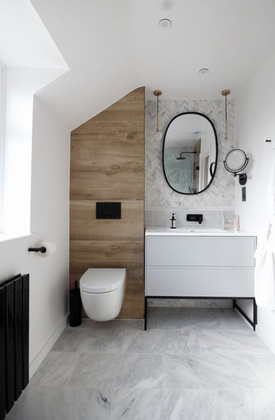 a small and chic bathroom clad with marble tiles, chevron and large scale ones, a wood look tile accent and black fixtures is stylish